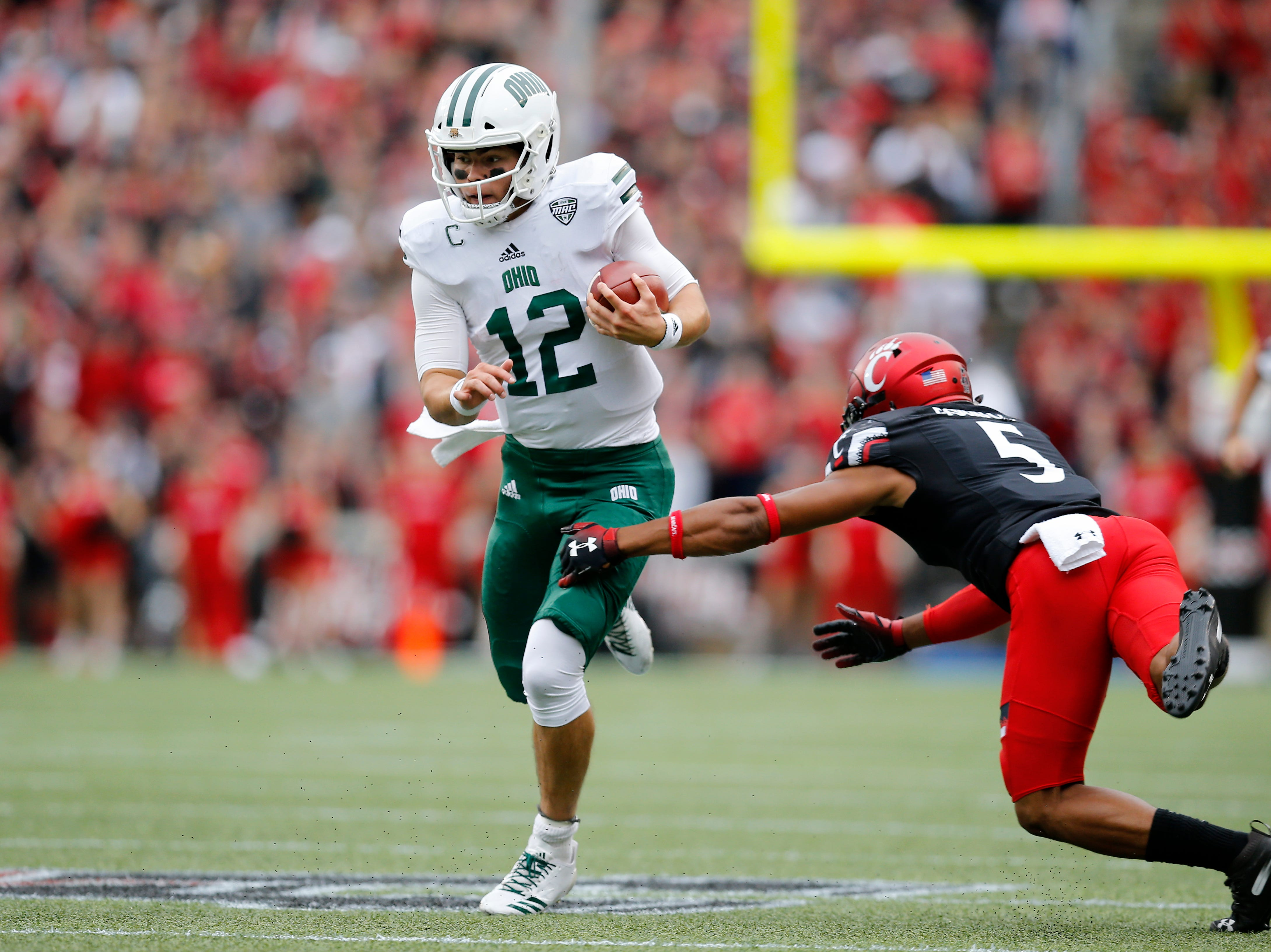 Ohio Bobcats quarterback Nathan Rourke (12) breaks a tackle from Cincinnati Bearcats safety Darrick Forrest (5) on a keeper in the first quarter of the NCAA football game between the Cincinnati Bearcats and the Ohio Bobcats at Nippert Stadium on the University of Cincinnati campus in Cincinnati on Saturday, Sept. 22, 2018. The Bobcats led 24-7 at halftime.