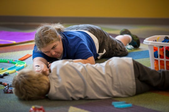 Sara Farris, a behavioral case manager, plays cars with an eight-year-old boy at the emergency shelter. It's sometimes impossible to find immediate foster-care placements for children removed from homes.
