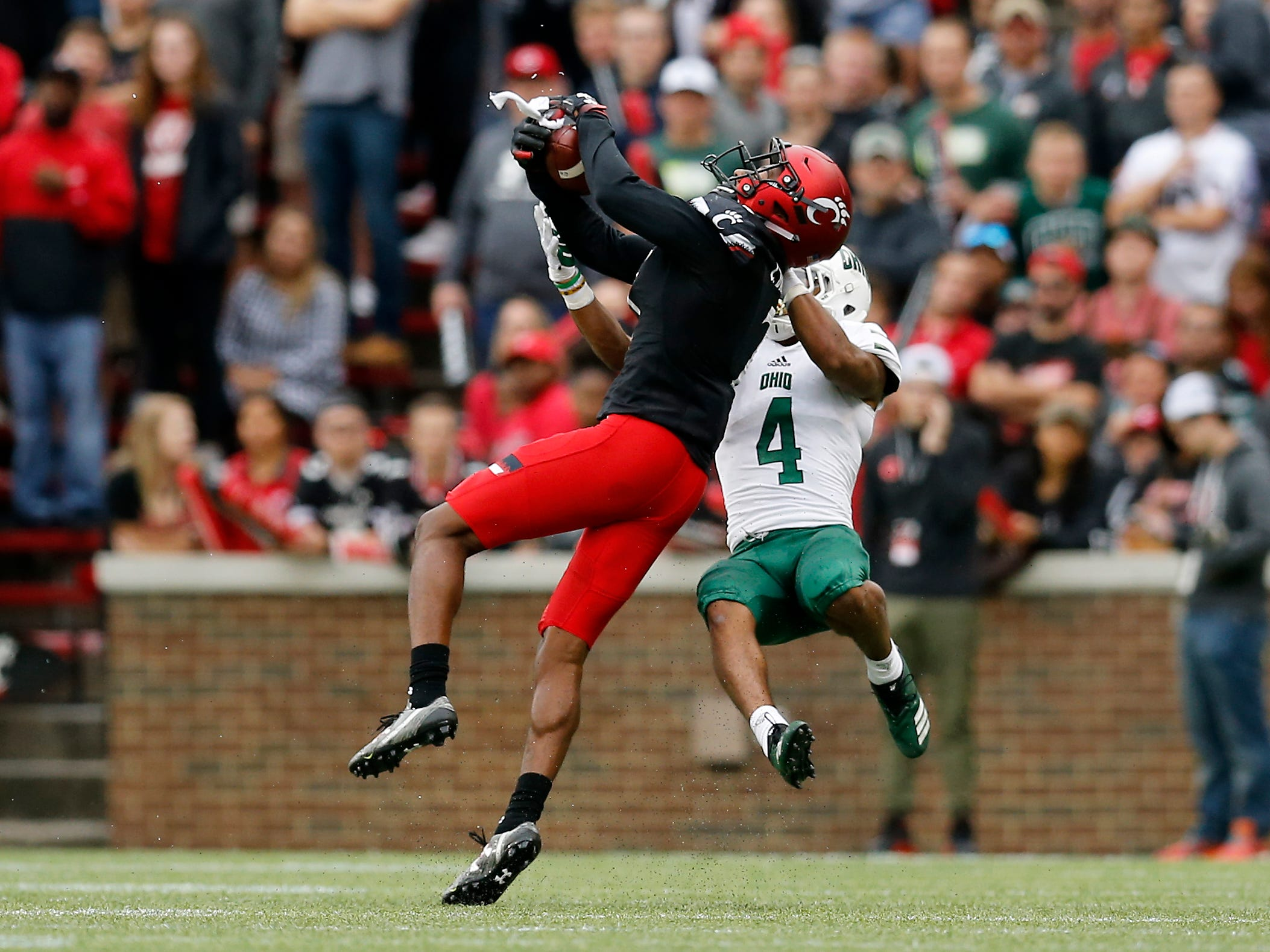 Cincinnati Bearcats cornerback Coby Bryant (7) nearly intercepts a pass intended for Ohio Bobcats wide receiver Papi White (4) in the second quarter of the NCAA football game between the Cincinnati Bearcats and the Ohio Bobcats at Nippert Stadium on the University of Cincinnati campus in Cincinnati on Saturday, Sept. 22, 2018. The Bobcats led 24-7 at halftime.