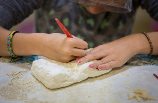 A 9-year-old girl works on a dinosaur-dig project. She says, 'You have to be patient' to dig out all the bones. She's been staying at the emergency placement center for about a week.. The center provides a home-like setting for children removed by Hamilton County Children's Services when the agency does not have an immediate home for them.
