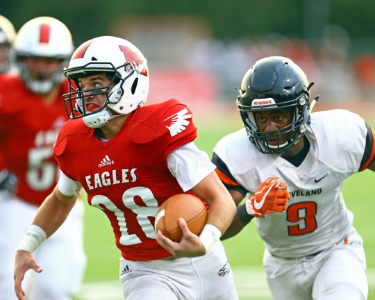 Milford running back Cameron Kells runs away from Loveland defensive back Natron Webster in the game between the Loveland Tigers and the Milford Eagles at Milford High School.