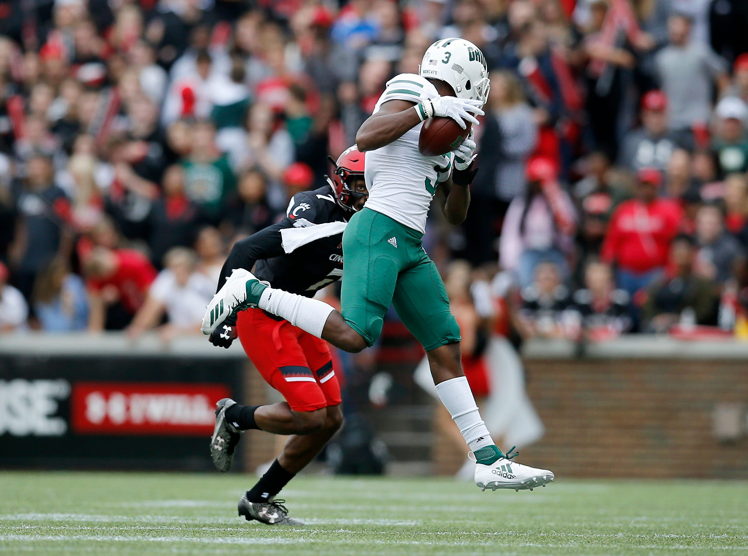 Ohio Bobcats wide receiver Cameron Odom (3) makes a catch ahead of Cincinnati Bearcats cornerback Coby Bryant (7) in the second quarter of the NCAA football game between the Cincinnati Bearcats and the Ohio Bobcats at Nippert Stadium on the University of Cincinnati campus in Cincinnati on Saturday, Sept. 22, 2018. The Bobcats led 24-7 at halftime.