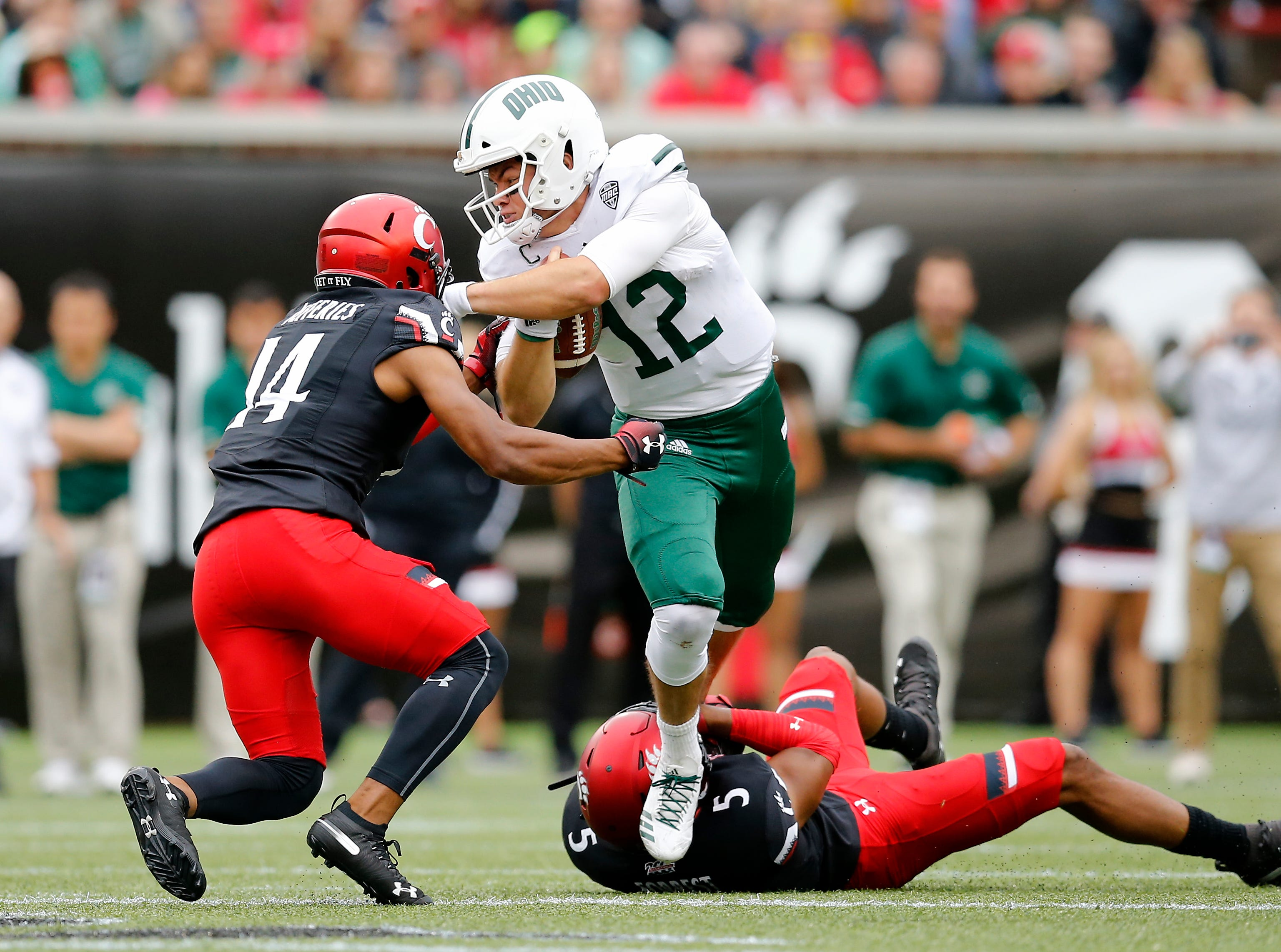 Ohio Bobcats quarterback Nathan Rourke (12) breaks a tackle in the first quarter of the NCAA football game between the Cincinnati Bearcats and the Ohio Bobcats at Nippert Stadium on the University of Cincinnati campus in Cincinnati on Saturday, Sept. 22, 2018. The Bobcats led 24-7 at halftime.