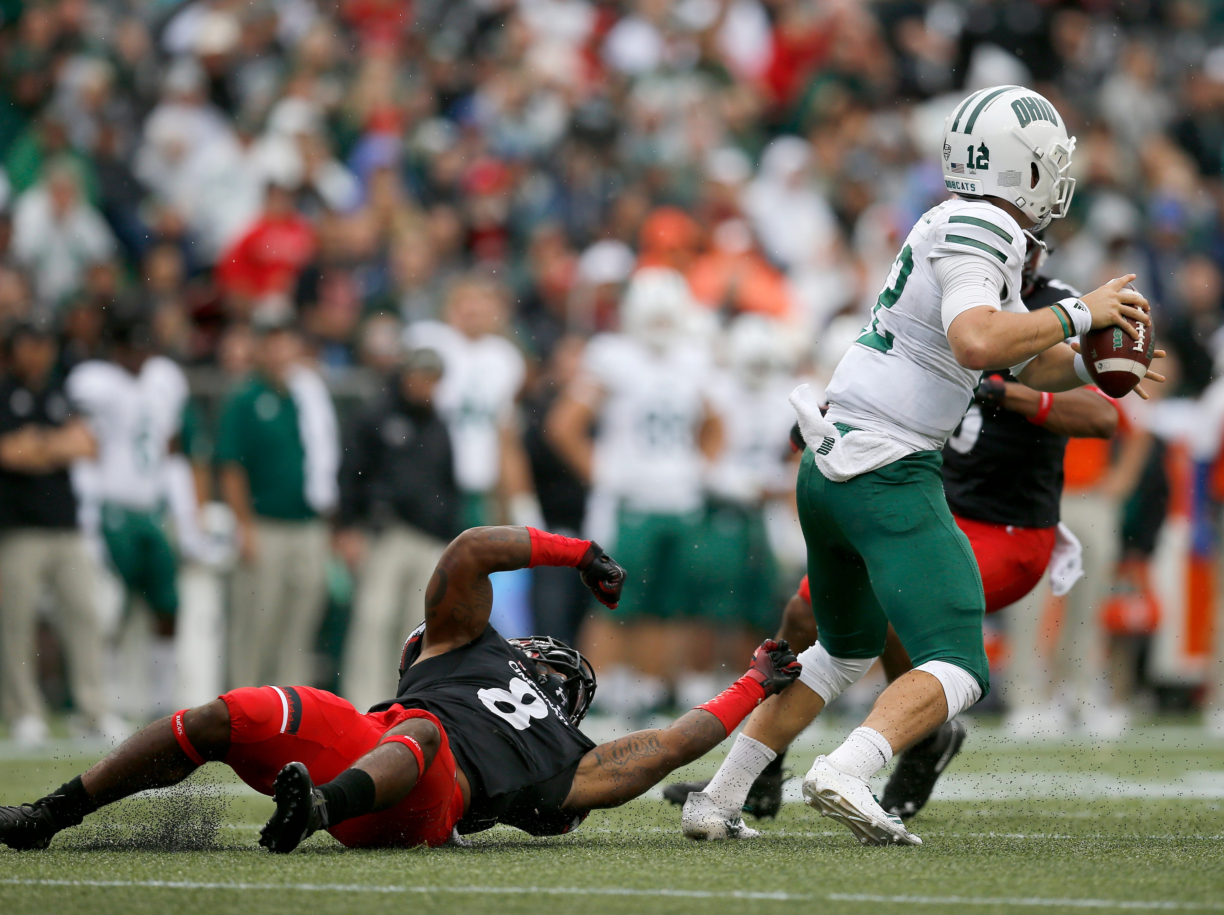 Ohio Bobcats quarterback Nathan Rourke (12) breaks a tackle from Cincinnati Bearcats linebacker Jarell White (8) in the second quarter of the NCAA football game between the Cincinnati Bearcats and the Ohio Bobcats at Nippert Stadium on the University of Cincinnati campus in Cincinnati on Saturday, Sept. 22, 2018. The Bobcats led 24-7 at halftime.