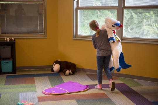 A nine-year-old girl carries one of the large stuffed animals in the play area at St. Joseph's Orphanage emergency shelter in Anderson Township. The children are closely supervised while playing and completing school lessons.