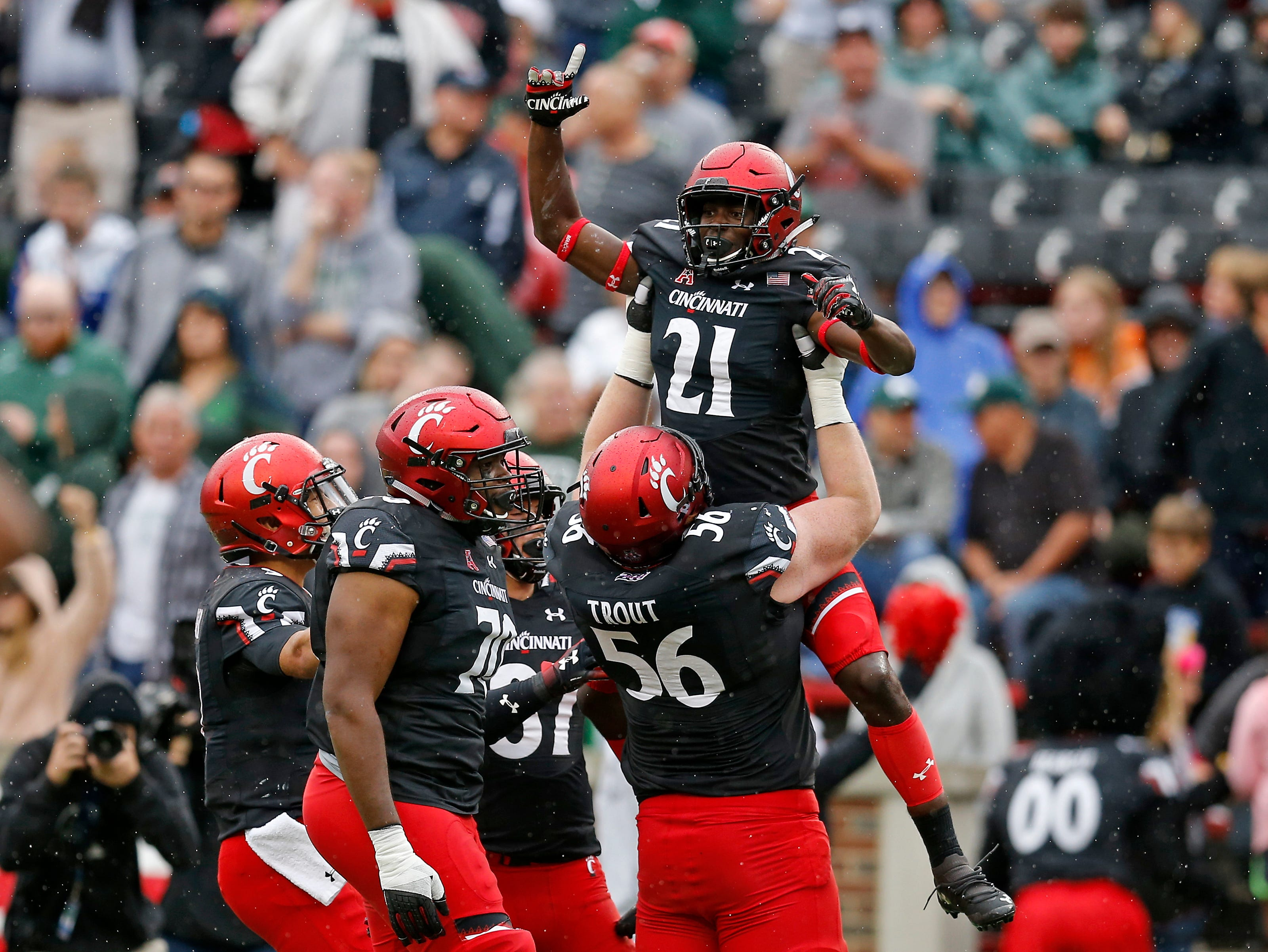Cincinnati Bearcats wide receiver Jayshon Jackson (21) is lifted by his team mates after scoring a touchdown in the fourth quarter of the NCAA football game between the Cincinnati Bearcats and the Ohio Bobcats at Nippert Stadium on the University of Cincinnati campus in Cincinnati on Saturday, Sept. 22, 2018. The Bearcats overcame a 24-7 deficit at halftime to win 34-30, improving to 4-0 on the season.