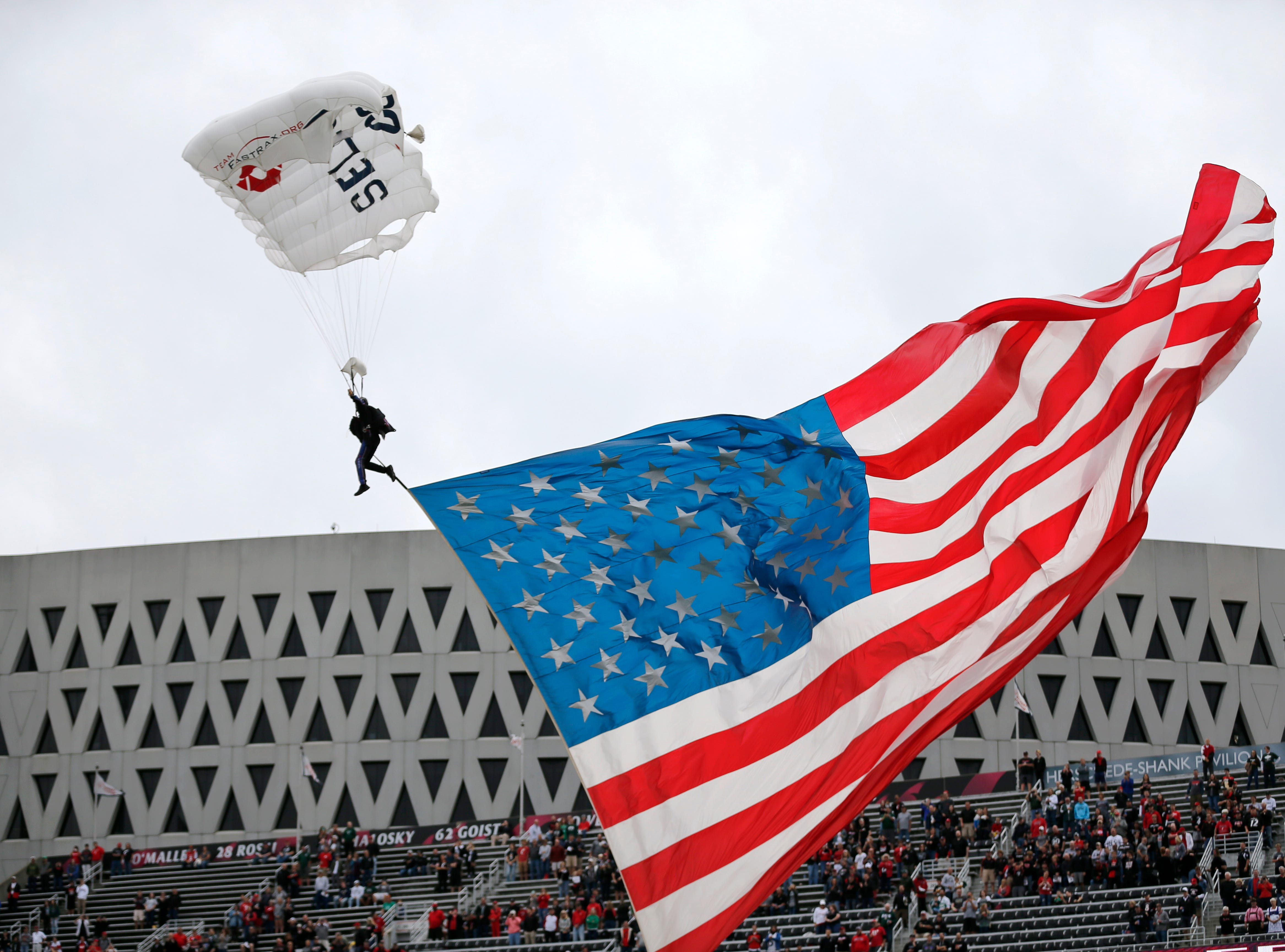 The American flag is delivered red by skydiver before the first quarter of the NCAA football game between the Cincinnati Bearcats and the Ohio Bobcats at Nippert Stadium on the University of Cincinnati campus in Cincinnati on Saturday, Sept. 22, 2018. The Bobcats led 24-7 at halftime.