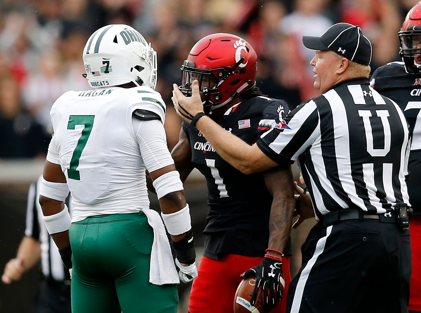 Ohio Bobcats safety Javon Hagan (7) and Cincinnati Bearcats wide receiver Kahlil Lewis (1) are separated by an official after a play in the second quarter of the NCAA football game between the Cincinnati Bearcats and the Ohio Bobcats at Nippert Stadium on the University of Cincinnati campus in Cincinnati on Saturday, Sept. 22, 2018. The Bobcats led 24-7 at halftime.