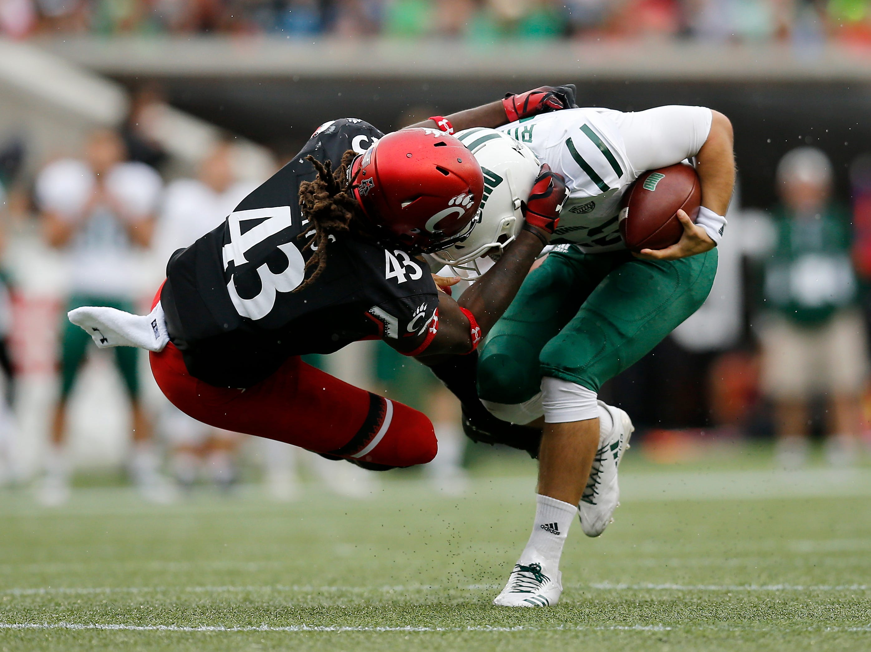 Ohio Bobcats quarterback Nathan Rourke (12) breaks a tackle from Cincinnati Bearcats defensive end Michael Pitts (43) in the second quarter of the NCAA football game between the Cincinnati Bearcats and the Ohio Bobcats at Nippert Stadium on the University of Cincinnati campus in Cincinnati on Saturday, Sept. 22, 2018. The Bobcats led 24-7 at halftime.