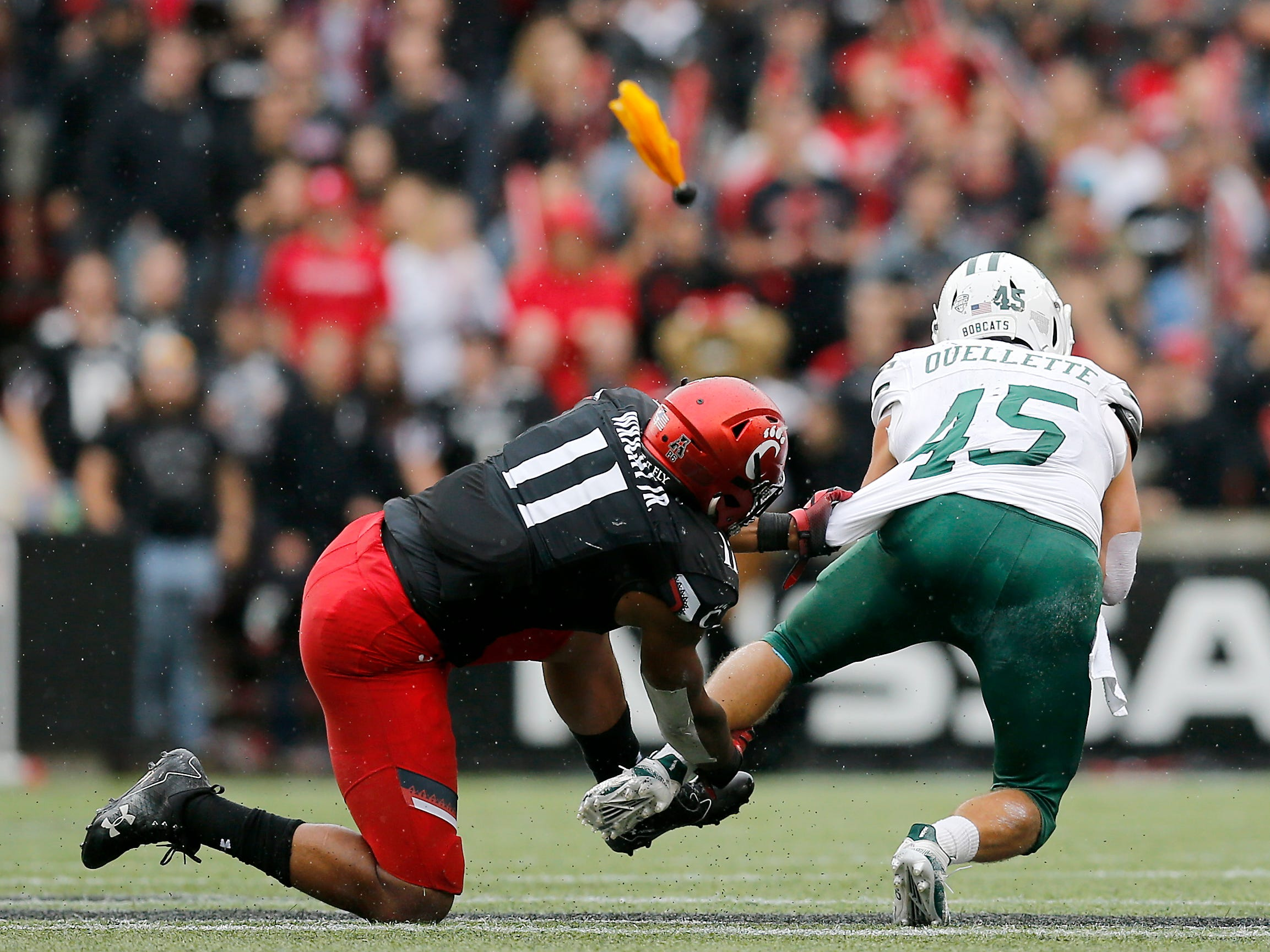 Ohio Bobcats running back A.J. Ouellette (45) is brought down by Cincinnati Bearcats linebacker Bryan Wright (11) as a flag flies in the third quarter of the NCAA football game between the Cincinnati Bearcats and the Ohio Bobcats at Nippert Stadium on the University of Cincinnati campus in Cincinnati on Saturday, Sept. 22, 2018. The Bearcats overcame a 24-7 deficit at halftime to win 34-30, improving to 4-0 on the season.