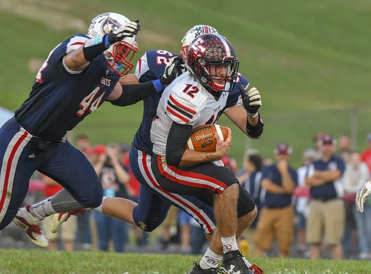 Trojan quarterback Alex Maxwell (12) gets away from two South Dearborn defenders, South Dearborn High School, Aurora, Indiana, Friday September 21, 2018