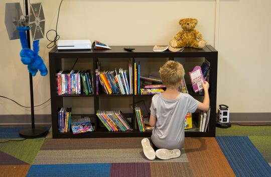 An 8-year-old boy chooses a book he can read to Willy, the worm he says he 'rescued' outside the St. Joseph Orphanage's Emergency Protection Program's doors while playing. The opioid crisis has prompted more child-protection cases.