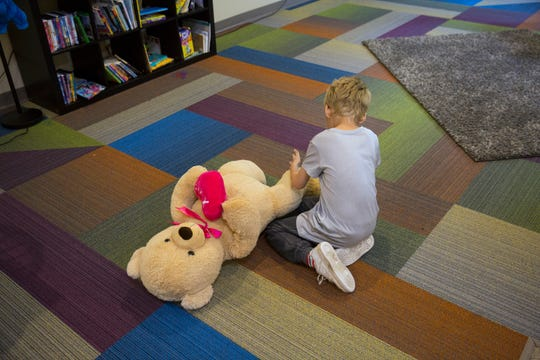 An eight-year-old boys plays on the floor at the St. Joseph's Orphanage emergency shelter in Anderson Township. The emergency shelter opened in January for children removed from home by Children Services. The opioid crisis has prompted more child-protection removals here and nationwide. Sometimes, it's impossible to find immediate foster-care placements for children removed. St. Joseph's emergency shelter takes siblings, individual children and even babies. The children are closely supervised while playing and completing school lessons.