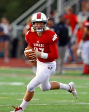 Milford quarterback Hunter Johnson rolls out to pass in the game between the Loveland Tigers and the Milford Eagles at Milford High School.