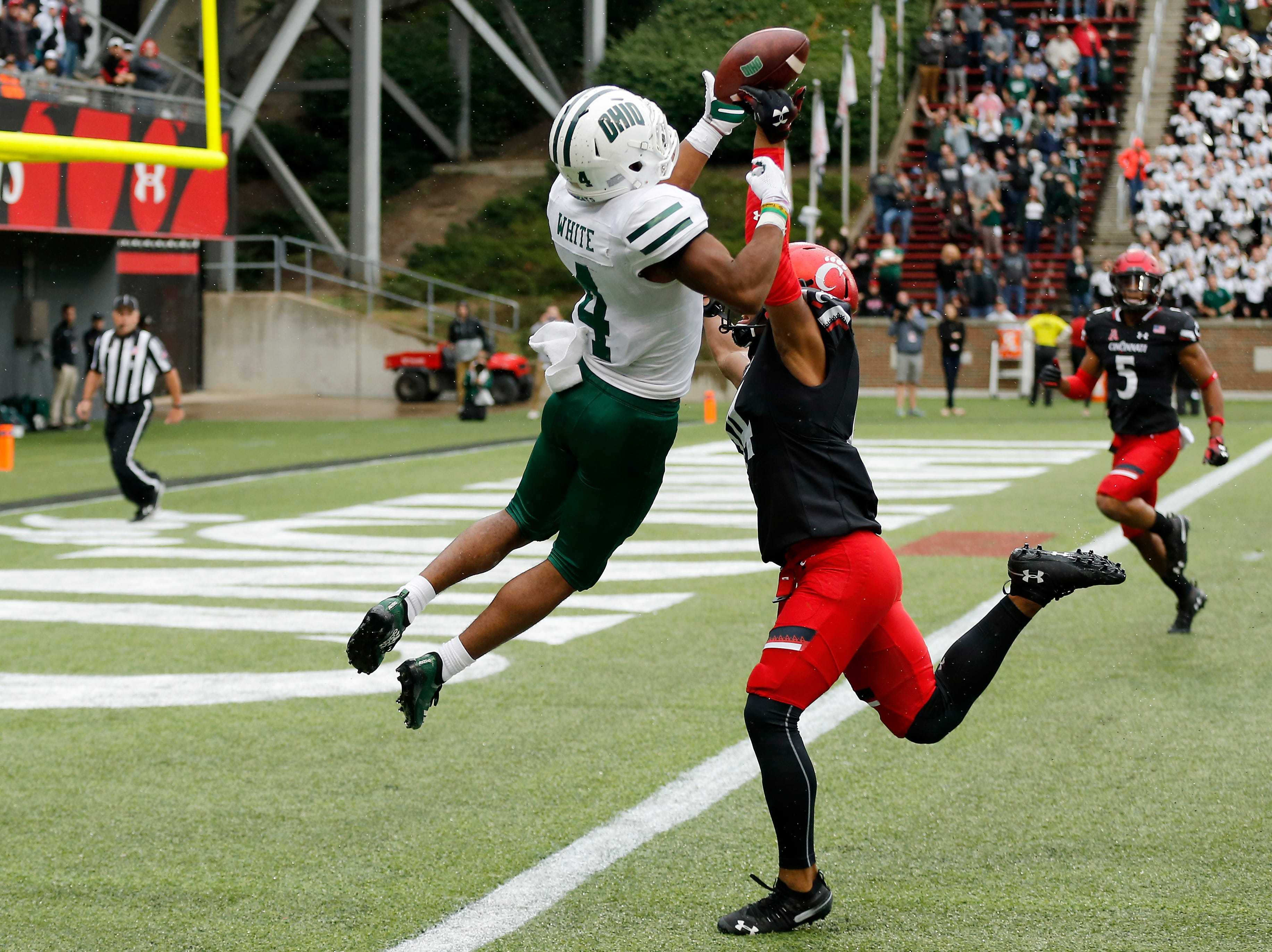 Cincinnati Bearcats cornerback Cameron Jefferies (14) breaks up a pass intended for Ohio Bobcats wide receiver Papi White (4) and is called for pass interference in the fourth quarter of the NCAA football game between the Cincinnati Bearcats and the Ohio Bobcats at Nippert Stadium on the University of Cincinnati campus in Cincinnati on Saturday, Sept. 22, 2018. The Bearcats overcame a 24-7 deficit at halftime to win 34-30, improving to 4-0 on the season.