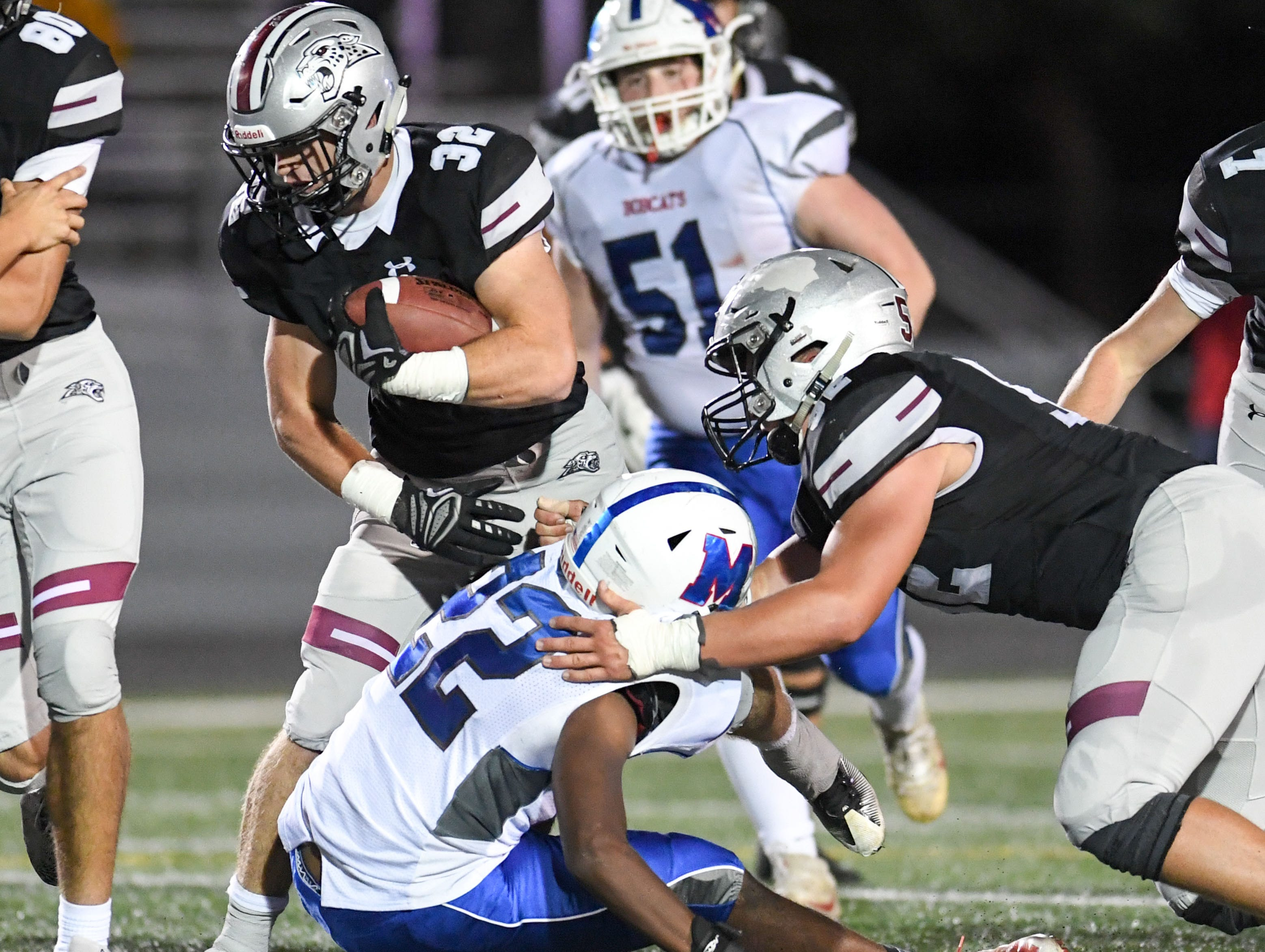 Ankeny Centennial's Gabe Godwin (32)  fights through Marshalltown defenders on Friday, Sept. 21, 2018 during a football game between the Ankeny Centennial Jaguars and the Marshalltown Bobcats at Northview Middle School.