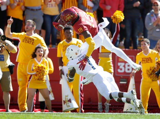 Iowa State wide receiver Hakeem Butler (18) dives over Akron defensive back Jordan George (7) during a 24-yard touchdown reception in the first half of an NCAA college football game, Saturday, Sept. 22, 2018, in Ames, Iowa.