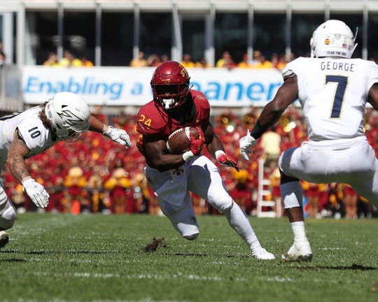 Sep 22, 2018; Ames, IA, USA; Iowa State Cyclones running back Johnnie Lang (24) avoids the tackle from Akron Zips linebacker Brian Bell (10) and defensive back Jordan George (7) at Jack Trice Stadium. The Cyclones beat the Zips 26 to 13.