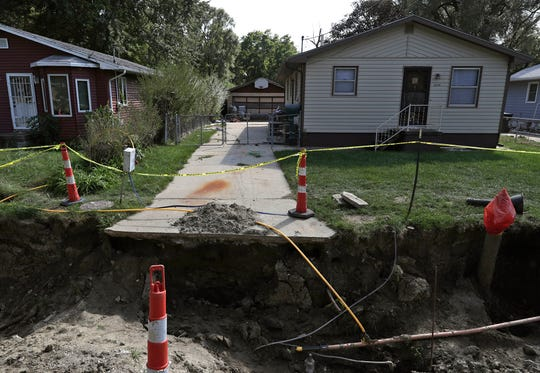 In this Thursday, Sept. 20, 2018 photo, the end of the driveway at 2645 Ave. L leads to a massive sinkhole caused by rising and falling water levels of the Missouri River, as well as rainfall, in Council Bluffs, Iowa. The Missouri River's fluctuating water levels are keeping crews busy fixing broken sewer lines and filling sinkholes around Council Bluffs. The Army Corps of Engineers believes the river will fluctuate between 23 feet (7 meters) and 28 feet (8.5 meters) deep over the next week. (Joe Shearer/The Daily Nonpareil via AP)