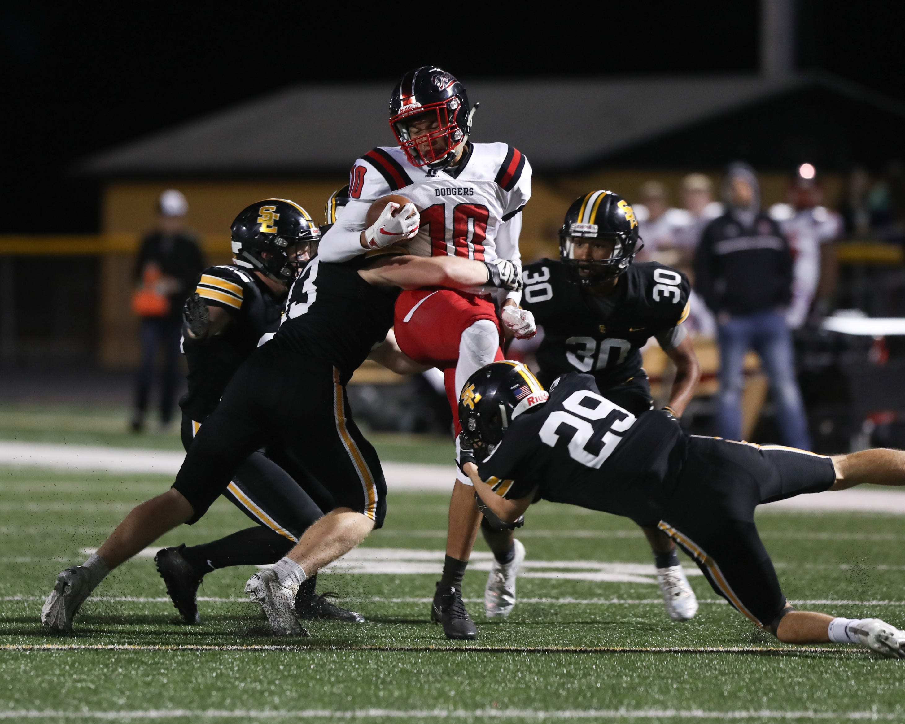 Fort Dodge Dodgers Tysen Kershaw (10) is tackled by a mess of Southeast Polk Rams at Ram Stadium.