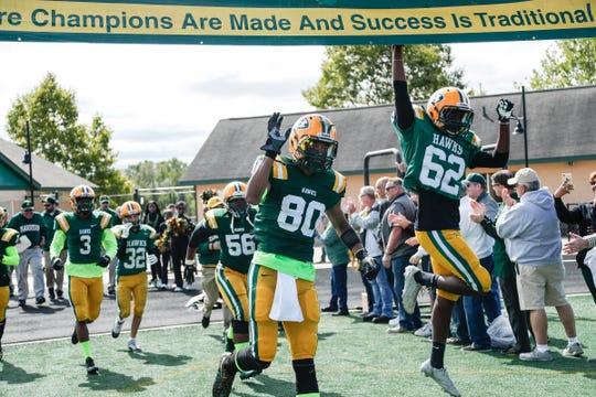 Farmington Hills Harrison players Trenton Ramsey (80) and Ken Rice (62) jump up to touch the banner before a game against Rochester Hills Stoney Creek at Harrison High School in Farmington Hills, Friday, September 21, 2018.
