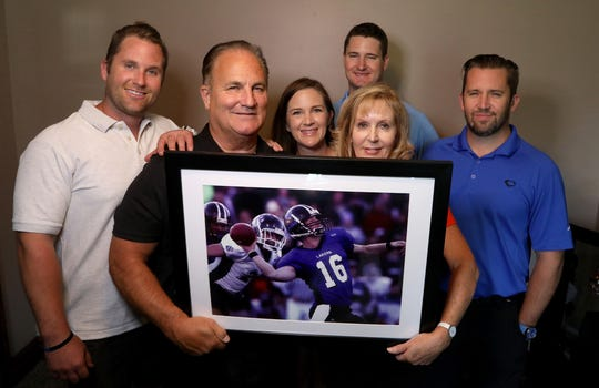 (From left) the Finnerty family, Brenden, Tim, Courtney Stewart, Maureen, brother-in-law Jon Stewart and Tim hold a picture of their brother and son, Cullen, at the family home in Brighton on July 20, 2018. Cullen was a quarterback at Grand Valley State University who died May 27, 2013 in the woods of Northern Michigan after getting lost and disoriented.