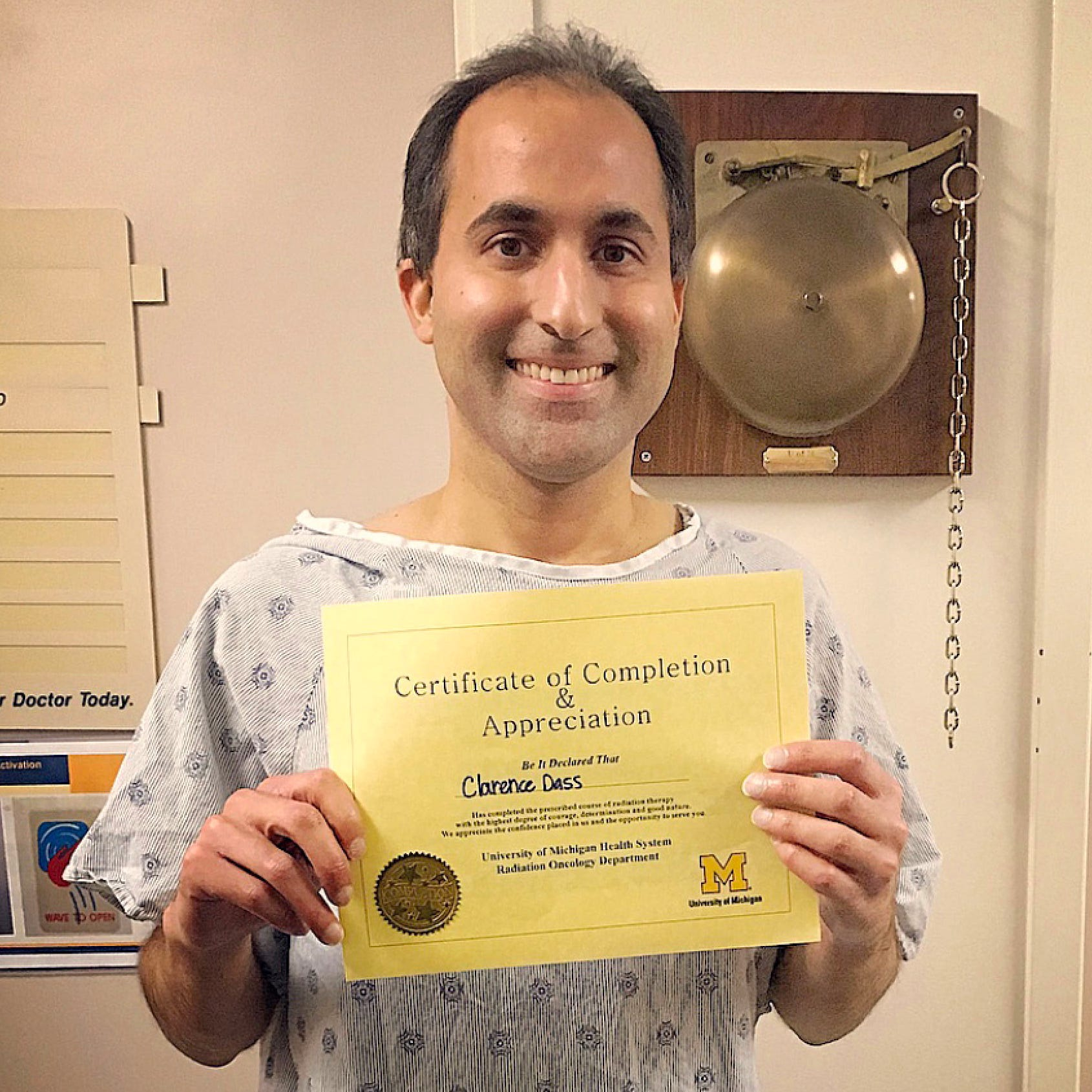 Clarence Dassholds a certificate on the day he finished treatment for stage 4 colon cancer