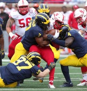 Michigan's Khaleke Hudson (7) and Reuben Jones (4) tackle Nebraska tight end Katerian Legrone on Sept. 22, 2018.