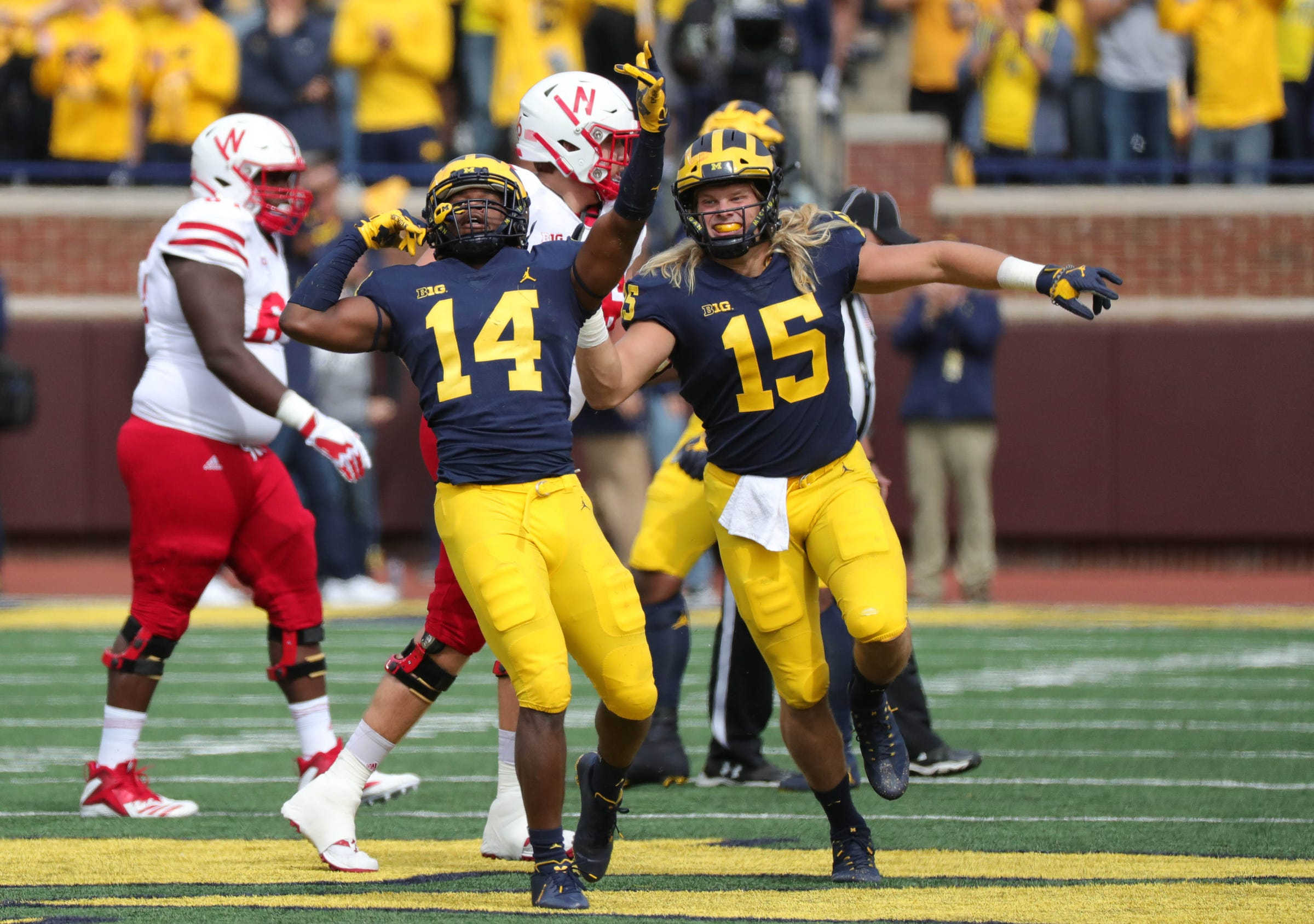 Michigan defenders Josh Metellus, left, celebrates with Chase Winovich after his interception against Nebraska quarterback Adrian Martinez during U-M's 56-10 win over Nebraska on Saturday, Sept. 22, 2018, at Michigan Stadium.