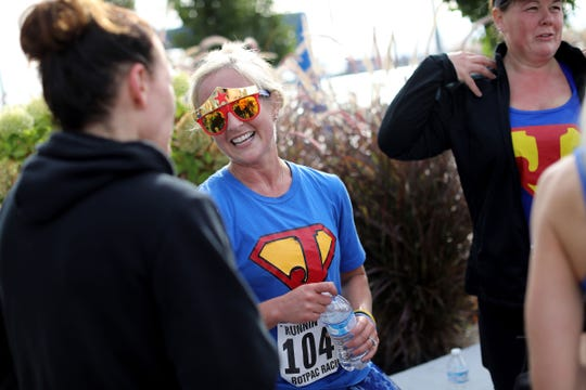 Jessica Cash, 35, of New Hudson talks with a group of friends who ran to support her in the 2018 Detroit Undy RunWalk on the Detroit Riverwalk on Saturday, Sept. 22, 2018. Cash was diagnosed with rectal cancer in 2015.