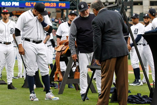 Victor Martinez wipes tears from his eyes as manager Ron Gardenhire and GM Al Avila present a framed jersey during his retirement ceremony before the game against the Royals.