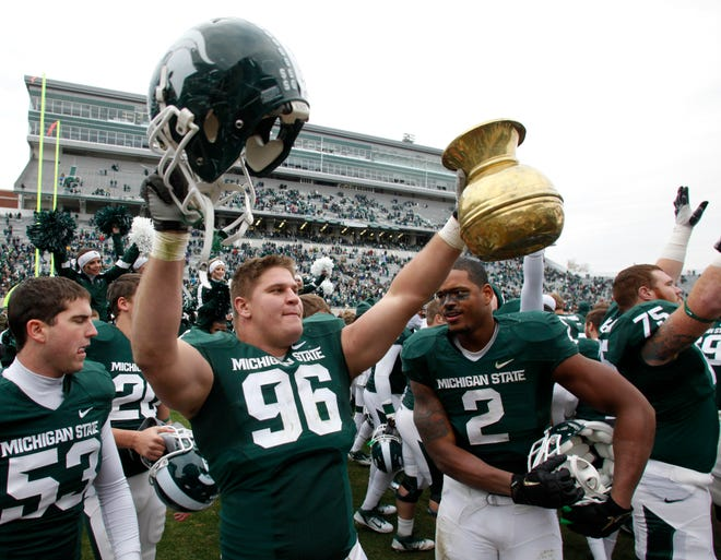 Michigan State's Kevin Pickelman (96) celebrates with the Old Brass Spittoon following a 55-3 win over Indiana in East Lansing, Nov. 19, 2011. The spittoon has been a coveted prize in this series since it was first awarded in 1950.