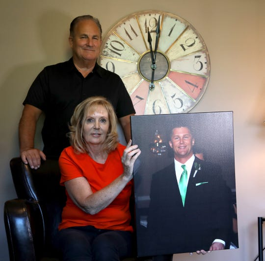 Tim and Maureen Finnerty, Cullen's parents, with a portrait of their son in their home in Brighton on July 20, 2018. Cullen was a quarterback at Grand Valley State University who died May 27, 2013, in the woods of Northern Michigan after getting lost and disoriented.