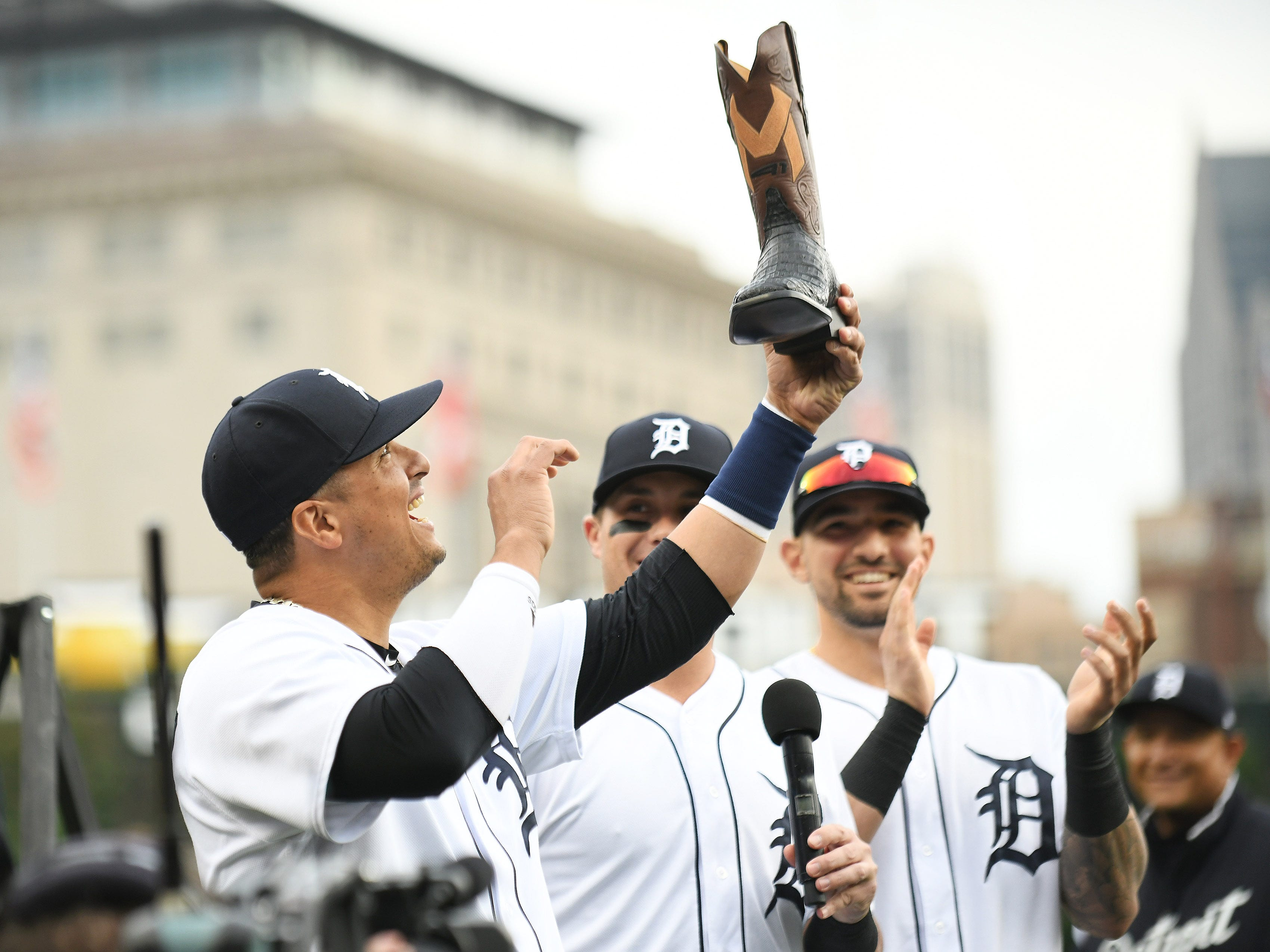 Tigers' Victor Martinez holds up one of the cowboy boots that the team got for him during a special tribute ceremony for Martinez before the game at Comerica Park in Detroit on Sept. 22, 2018.