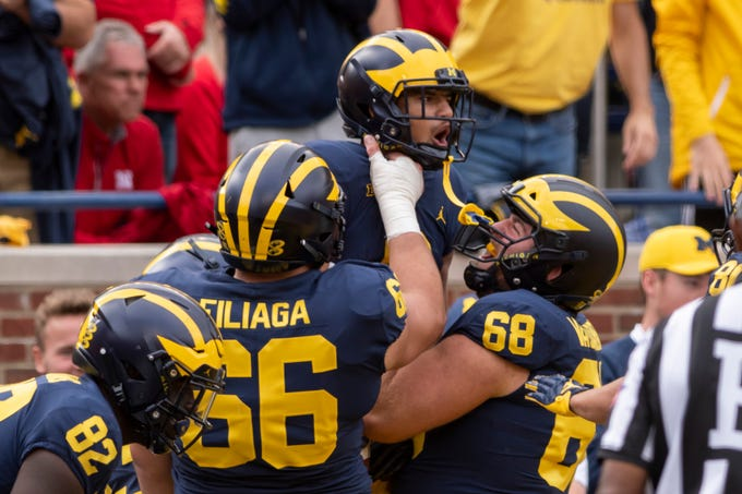 Michigan wide receiver Ronnie Bell is lifted into the air after catching a touchdown pass in the fourth quarter.