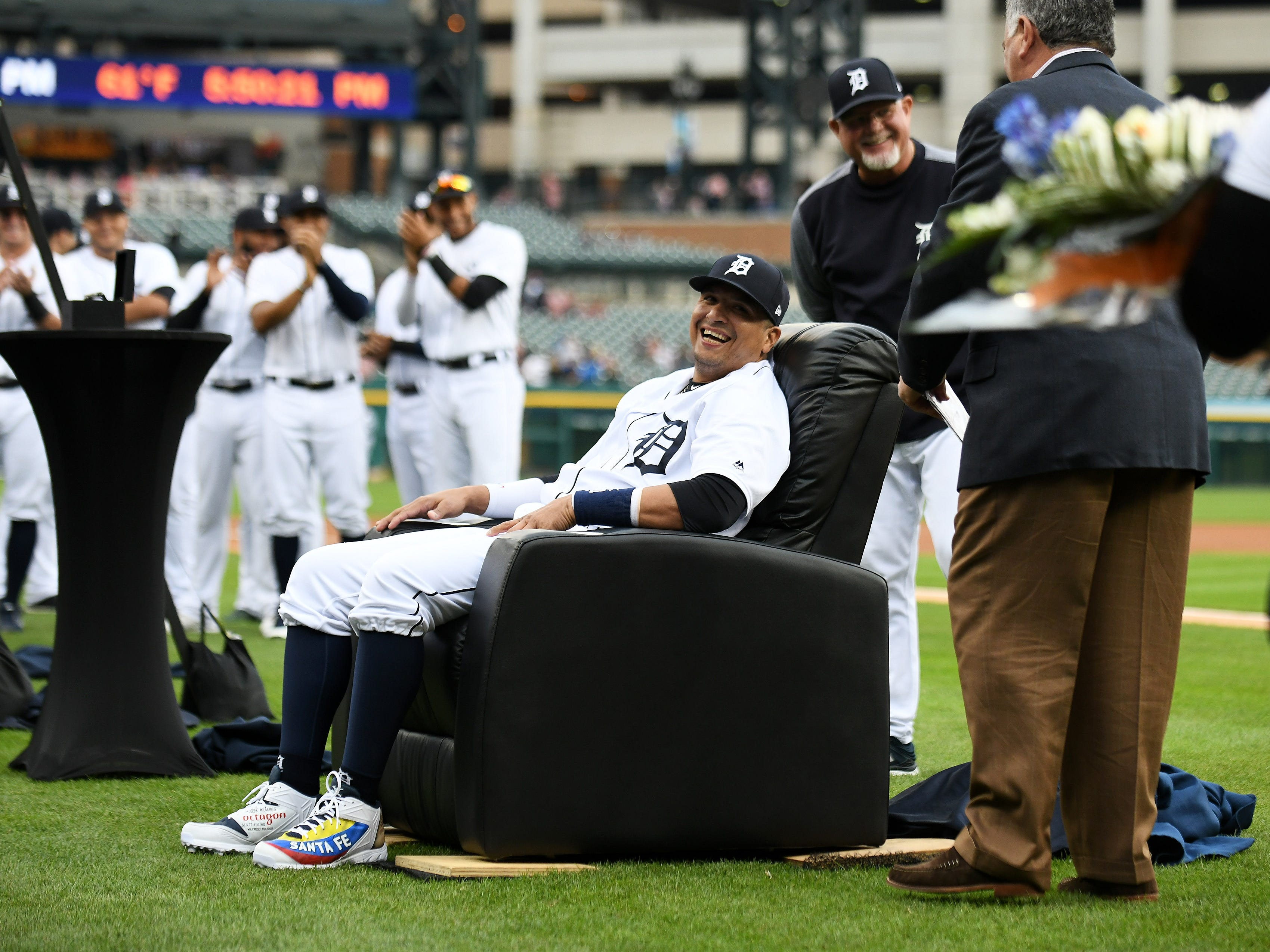 His teammates applaud while Tigers' Victor Martinez sits in a recliner that is given to him during a special tribute ceremony.