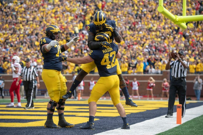 From left, Michigan offensive lineman Ben Bredeson, tight end Nick Eubanks, and fullback Ben Mason celebrate Mason's first touchdown of the day in the first quarter against Nebraska.