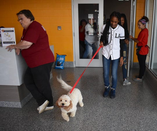 "Jasmin Thomaston, 14, Detroit, leaves the animal shelter with five-year-old ""Oliver,"" her new dog."