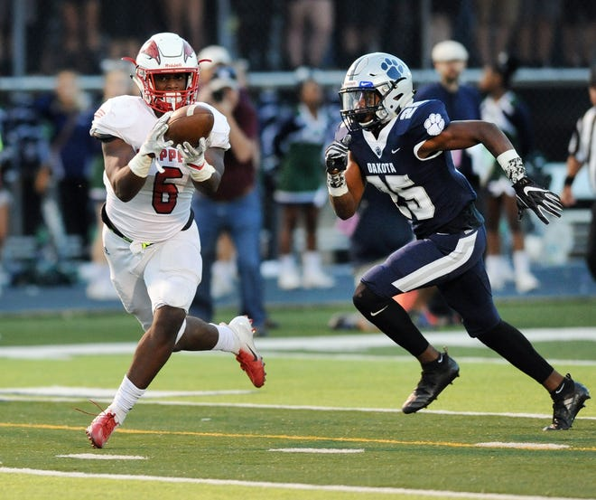 Clinton Township Chippewa Valley tight end Marcel Lewis, left, hauls in a pass and runs in for a touchdown past Macomb Dakota defensive back De'Javion Stepney (25) in the first quarter on Friday.
