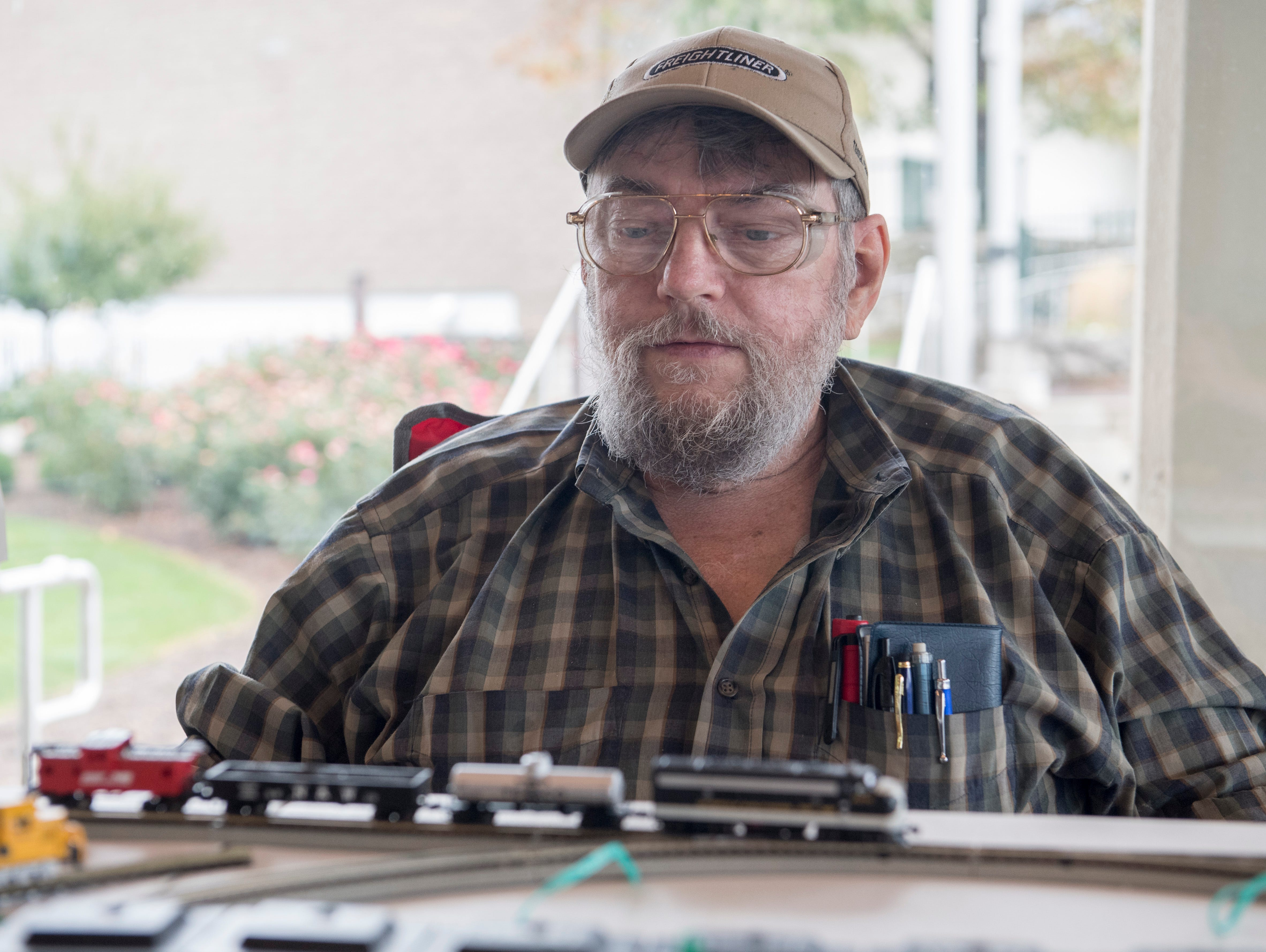 Neal Wayman, a 50 year enthusiast of model trains, adjusts an n gauge train set during the Local Loco Model Railroad Club show at the Evansville Pagoda Sept. 22, 2018.