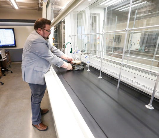 Assistant Professor Jason Kowalski assembles a distillation set-up in the new Dr. Richard and Leslie Ridenour Science Center on the Marian University campus.