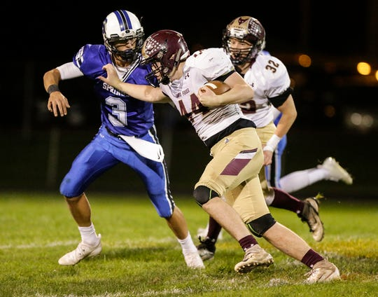 St, Mary's Springs' Mitchell Waechter moves in to tackle Omro's Zac Boese on Friday at Fruth Field.