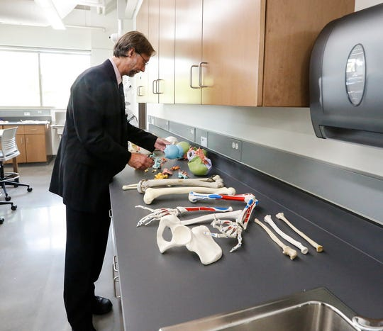 Anatomy and physiology professor Dr. Lance Urven sets out real and artificial human bones in the new Dr. Richard and Leslie Ridenour Science Center on the Marian University campus.