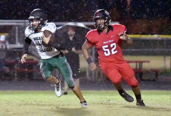 Palmetto Ridge High School Evan Rodriguez (15) runs the ball with South Fort Myers defensive linemen Tzion Hamilton (52) looking to make the tackle during their game in Fort Myers ,Friday, Sept. 21, 2018.