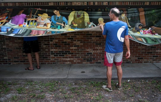 """Scott Hudson helps install the """"Modern Last Supper"""" mural onto a building near the corner of Carrell Road and Broadway in Fort Myers on Thursday."""