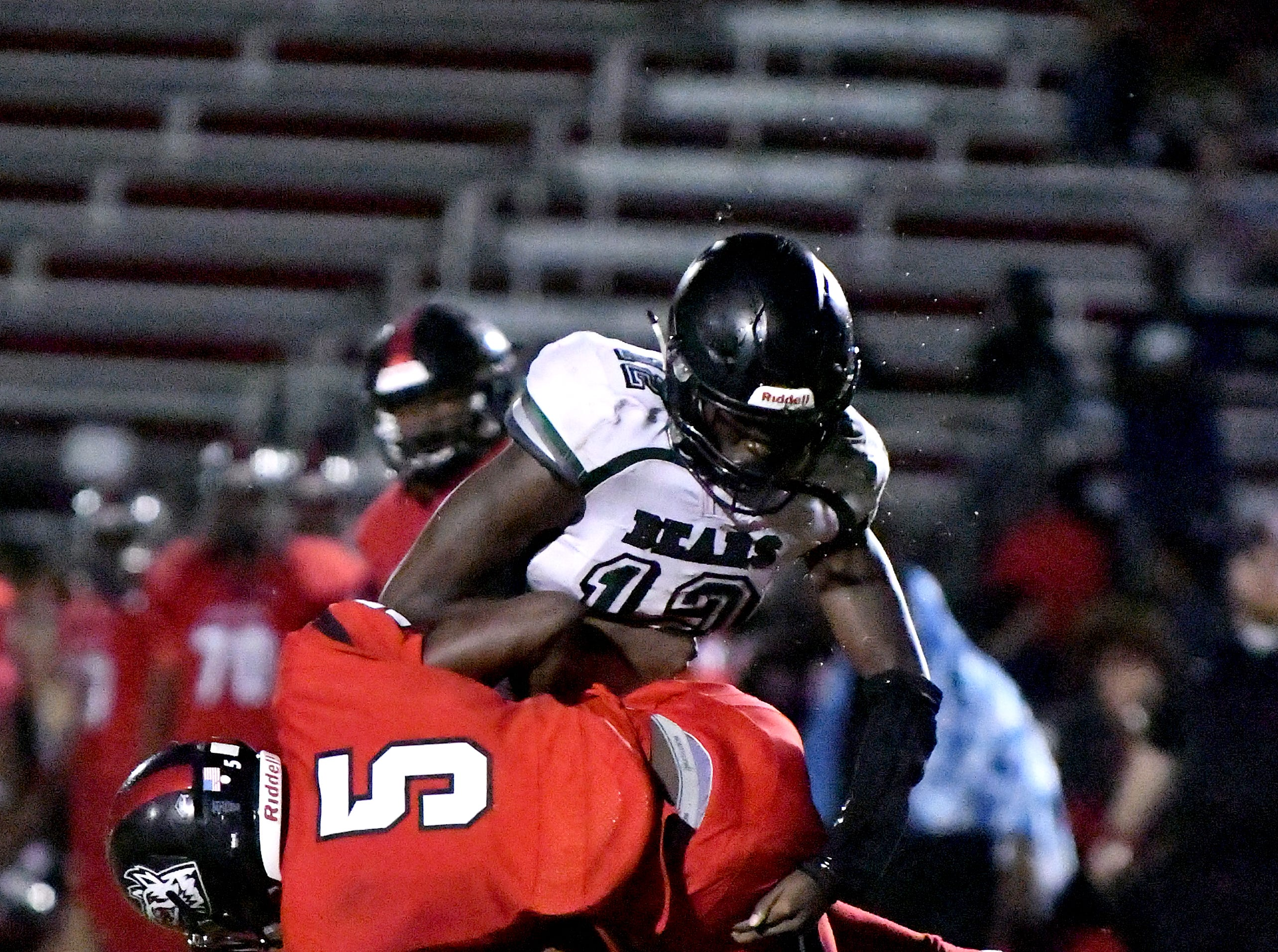 South Fort Myers High School Quincy Milhomme (5) is stopped by two Palmetto Ridge High School defenders during game in Fort Myers ,Friday, Sept. 21, 2018.