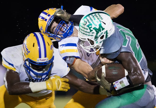 Fort Myers High School's Milan Tucker, right, takes on Charlotte defenders on Friday at Fort Myers.