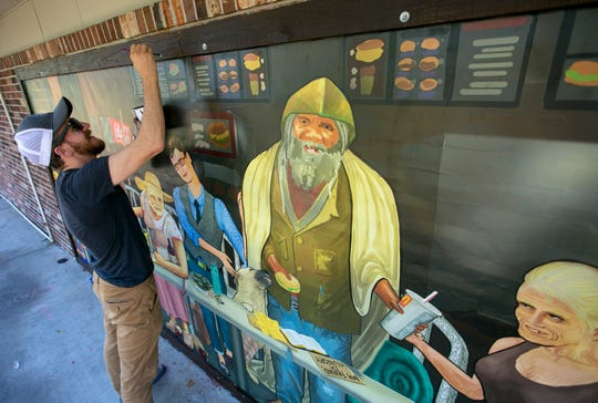 """Atlanta artist Ross Boone puts the finishing touches on the frame surrounding his mural that was installed on Thursday and Friday on a building facing Carrell Road in Fort Myers near the intersection with Broadway. The artwork is titled, """" Modern Last Supper."""""""