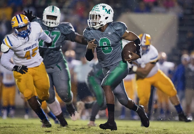 Fort Myers High School's Willie Neal eludes Charlotte defenders on Friday at Fort Myers. Charlotte beat Fort Myers 28-20.