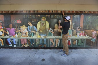 "Atlanta artist Ross Boone also known as Raw Spoon places his mural on a building in Fort Myers. The artwork is titled, ""Modern Last Supper."""